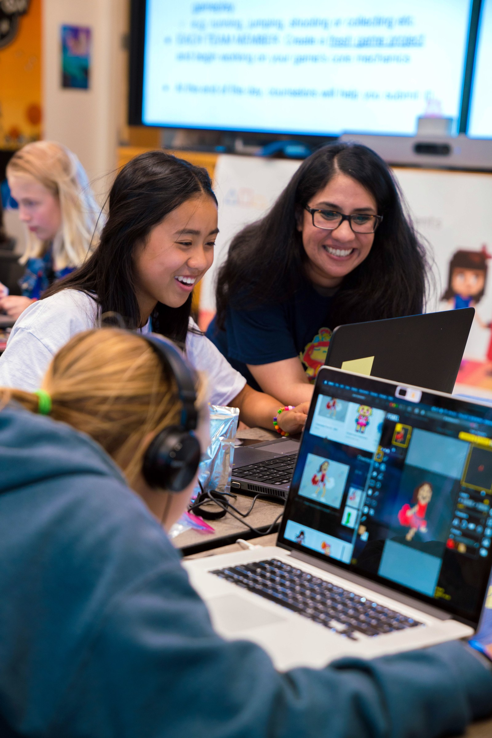 image shows a young woman smiling while the founder of Girls Make Games looks on over her left shoulder. Other girls are visible in the background and in the extreme foreground. They are working intently at laptops.